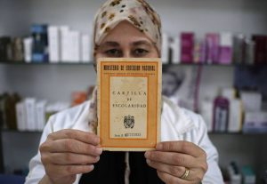 فاطمة-إسم وهمي- تشهر بطاقتها المدرسية.. المصدر: إِلْباييس